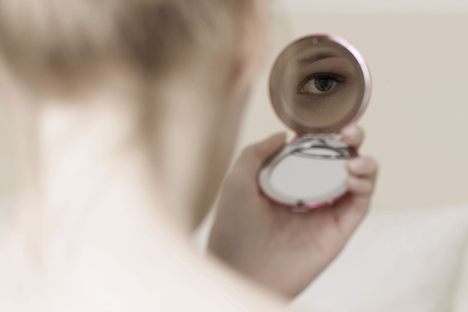 A person looks at their face in a compact mirror.