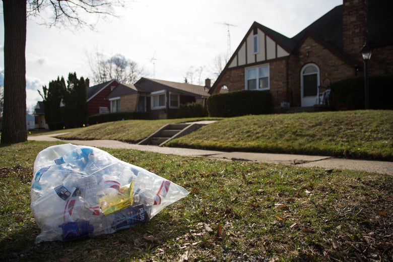 A clear trash bag filled with empty water bottles and water filters on the grass outside of a house.