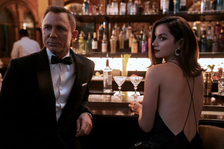 On the left, a blond man wears a tuxedo and looks to his right. He leans on a bar. Next to him is a woman with long brown hair and a strappy black dress, who holds a glass and sits at the bar. She looks in the same direction.