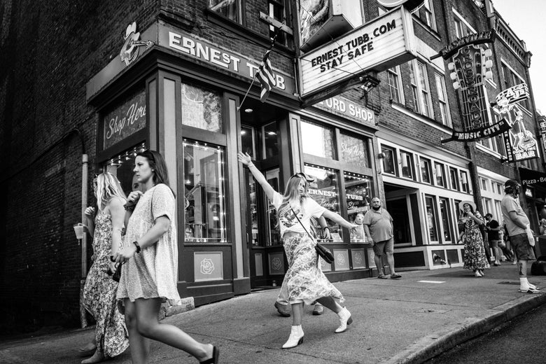 A black-and-white photo of women partying on Broadway in Nashville.