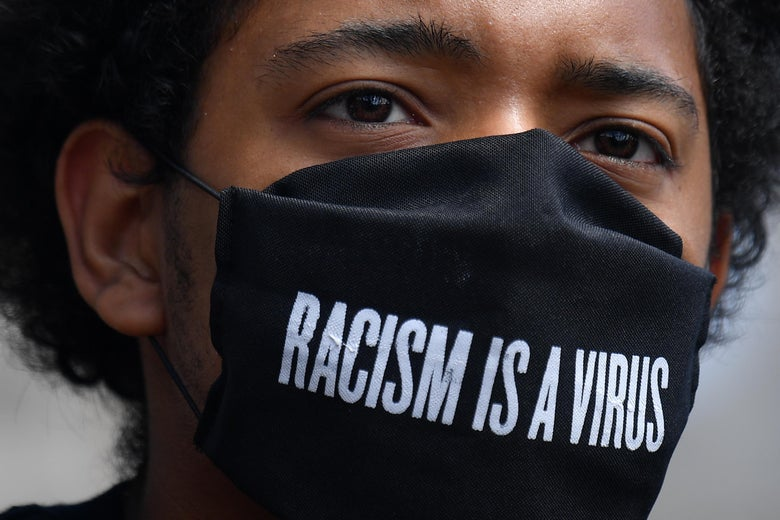 "A protester wears a protective face covering with the slogan ""Racism is a Virus"" written on the fabric as he listens to speeches at a gathering in support of the Black Lives Matter movement at Marble Arch in London on July 5, 2020."