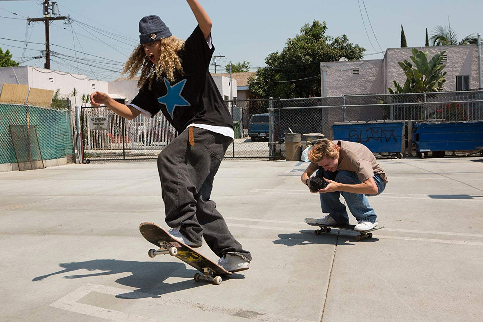A kid films another kid on a skateboard.