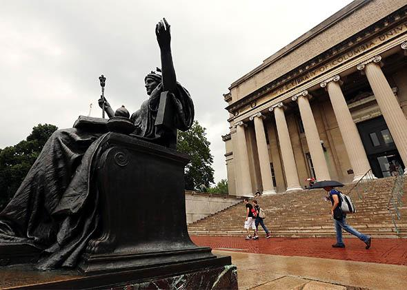 People walk past the Alma Mater statue at Columbia University.