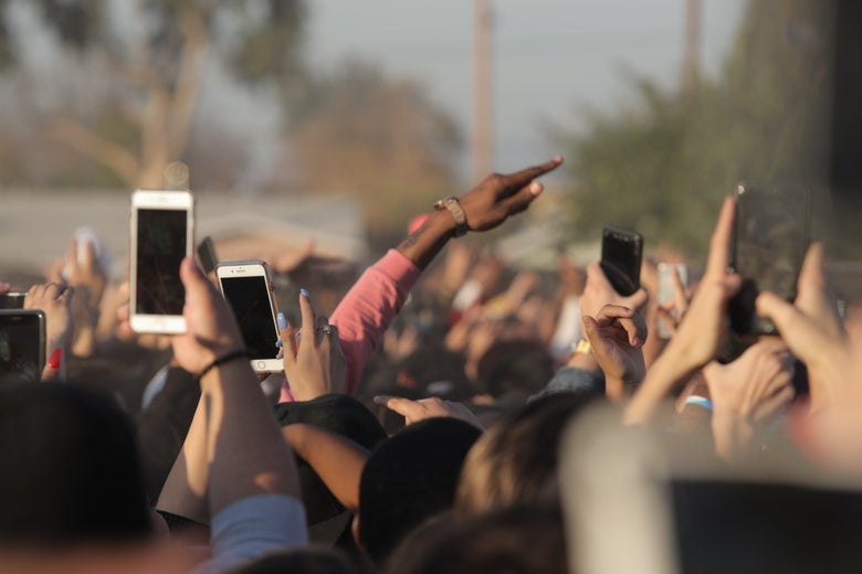 People in a crowd raise their arms and their phones.