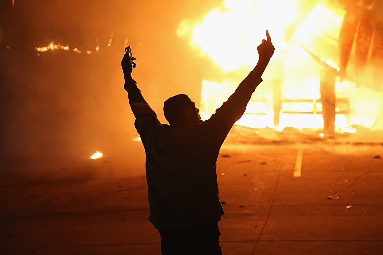A demonstrator celebrates as a business burns during rioting following the grand jury announcement in the Michael Brown case on Nov. 24, 2014 in Ferguson, Missouri.