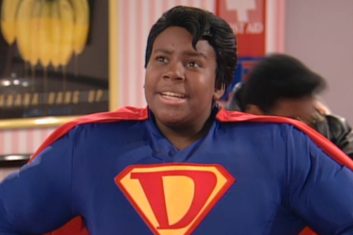 A young Kenan Thompson wears a Superman-like suit with a D on the chest.
