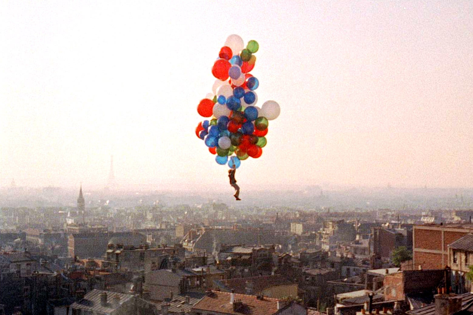 In a still from The Red Balloon, Pascal Lamorisse glides above a city, kept aloft only by the cloud of balloons he's holding onto.