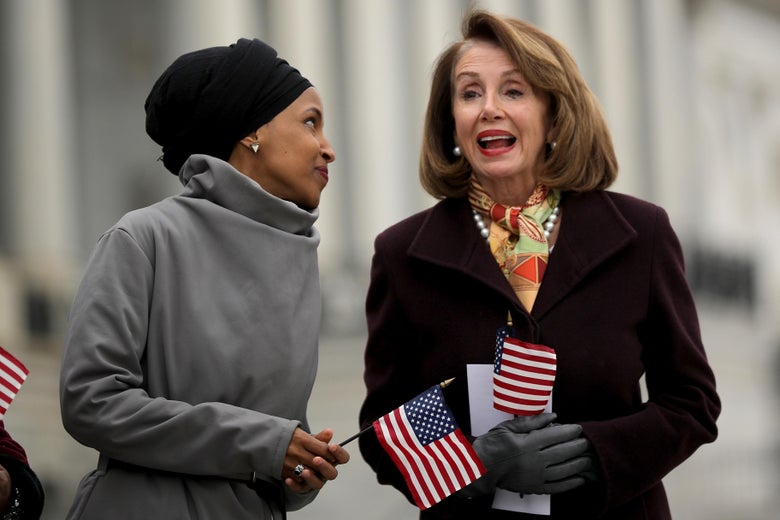 Rep. Ilhan Omar talks with Speaker of the House Nancy Pelosi on the east steps of the U.S. Capitol. Both women are holding small American flags.