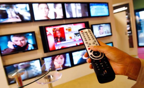 A visitor uses a remote control as she looks at television programmes during the annual MIPCOM television programme market in Cannes, southeastern France, October 4, 2010.