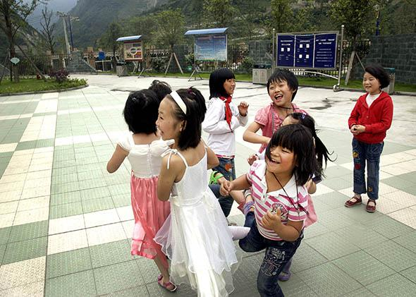 A group of girls plays a game at Xingxing primary school on June