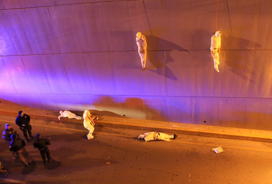 Police and forensic technicians stand near the wrapped bodies of two unidentified men hanging from an overpass as three more bodies lie on the ground in Saltillo, Mexico, on March 8, 2013. Five corpses wrapped head to toe in white sheets were found early Friday on a highway in the northern Mexican city of Saltillo, victims of suspected gang-related slaying. The attorney general's office of Coahuila state said three of the bodies were hung by rope from a bridge and two were on the ground. All were male and lacked identification.