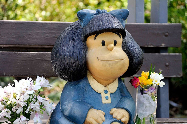 A statue depicting Mafalda is seen on a bench and near some flowers.