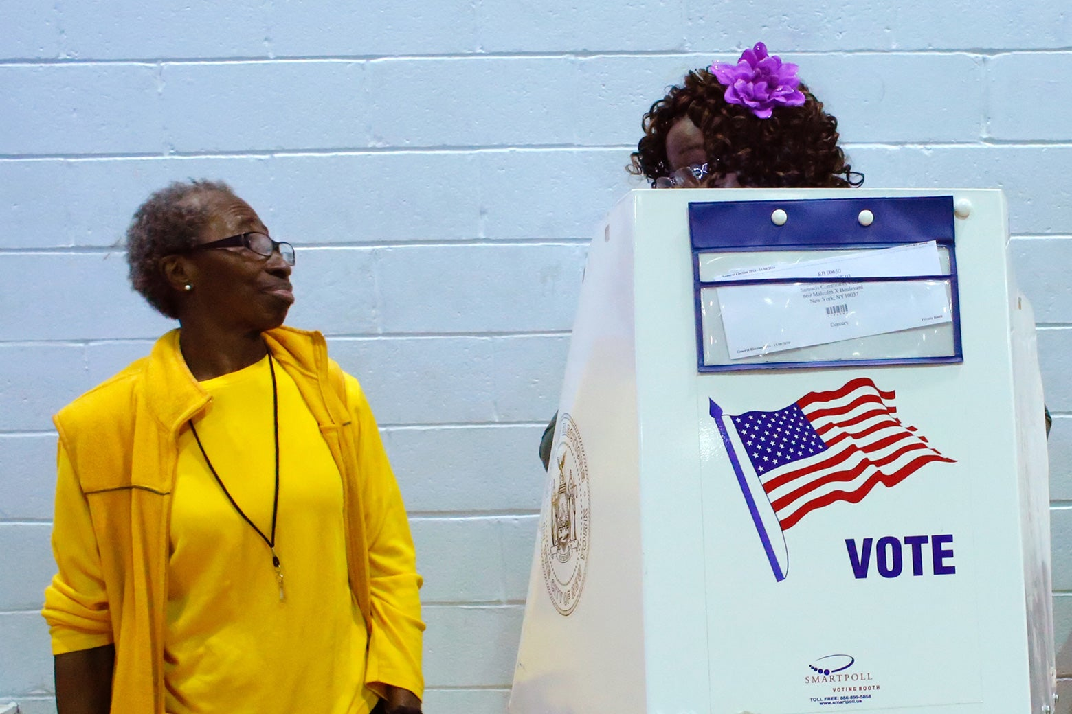 A voter asks an election worker a question as she votes at Samuels Community Center in the presidential election November 8, 2016 in the Harlem neighborhood of New York City.