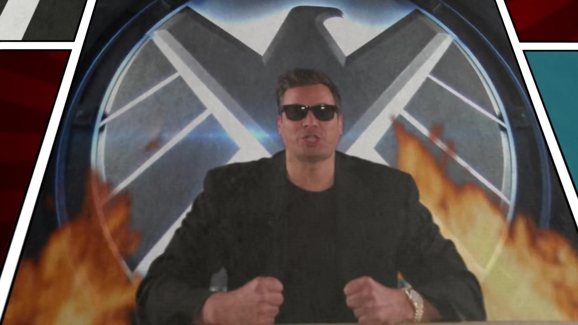 Jimmy Fallon, dressed as Billy Joel, in front of a burning logo from Marvel's S.H.I.E.L.D.