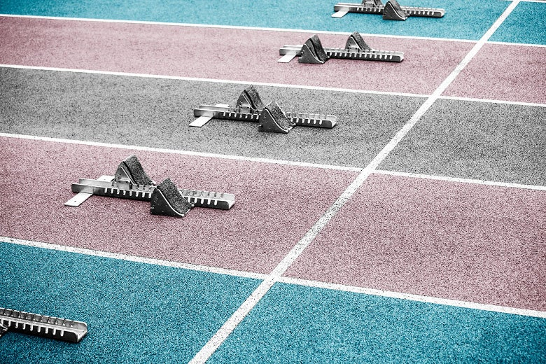 A high school track with lanes painted light blue, pink, and white, the colors of the transgender flag, and starting blocks in each lane
