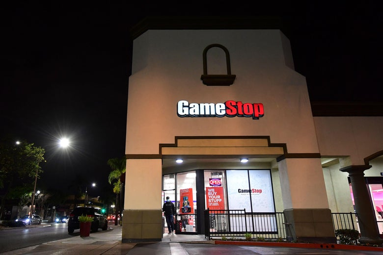 A man stands outside a GameStop store at night.