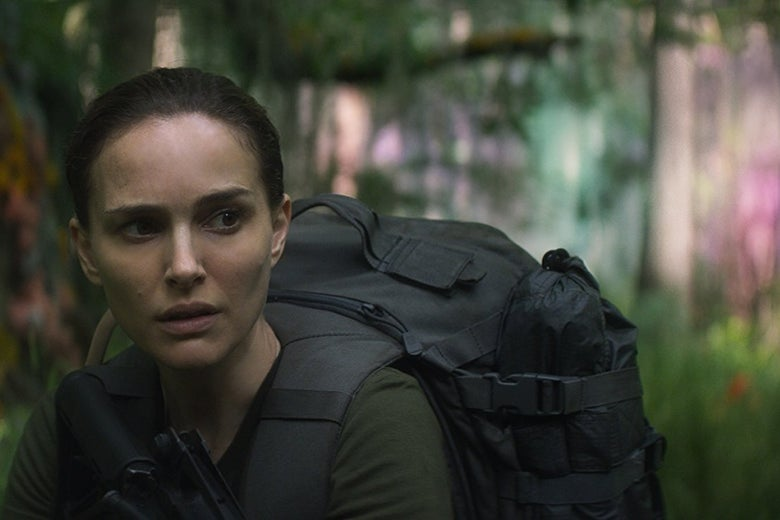 Natalie Portman wears fatigues and holds a gun in a shimmering forest