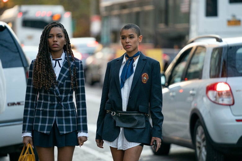 Two girls in prep school uniforms stand on a busy New York street between cars
