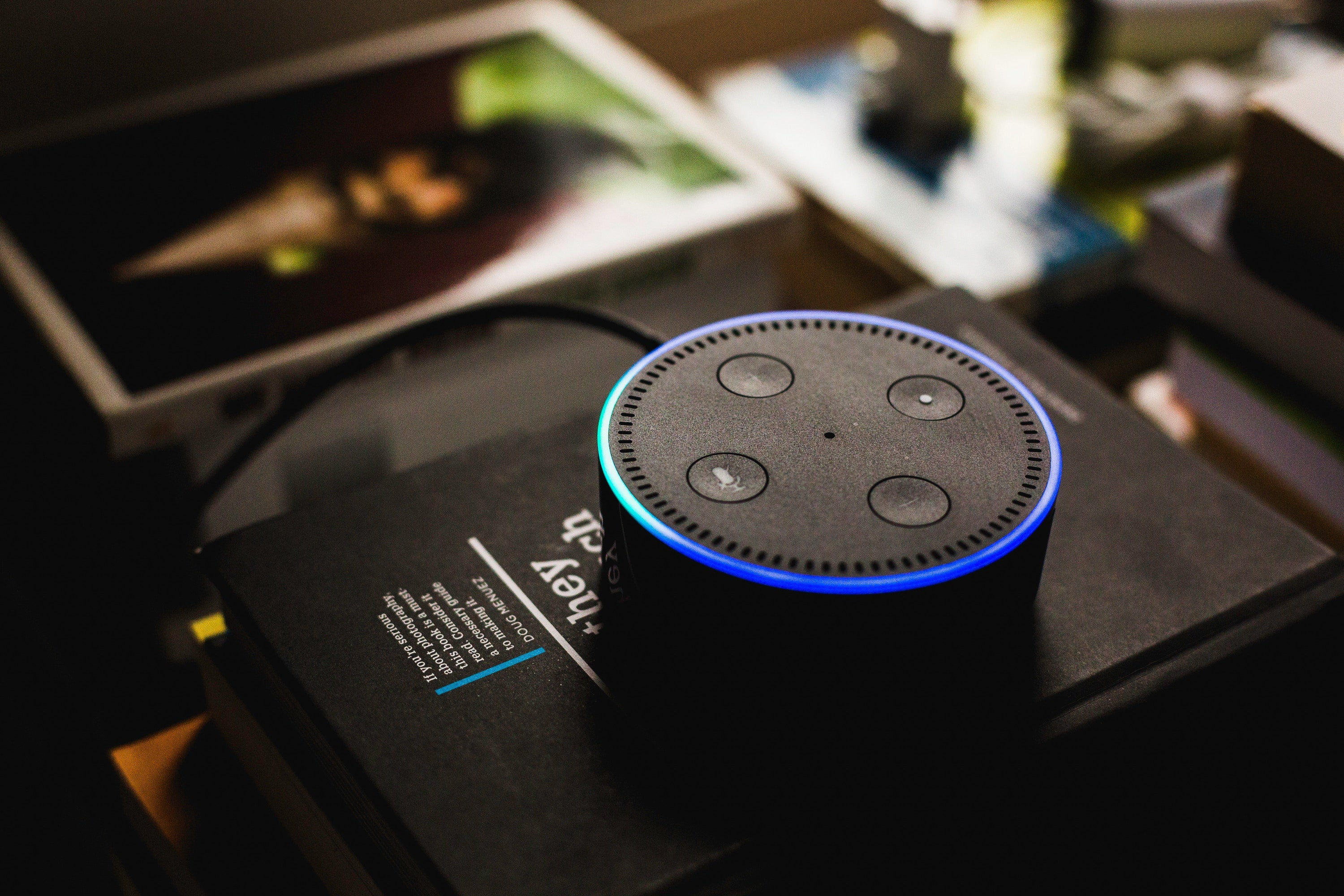 An Echo dot sits on a pile of books.