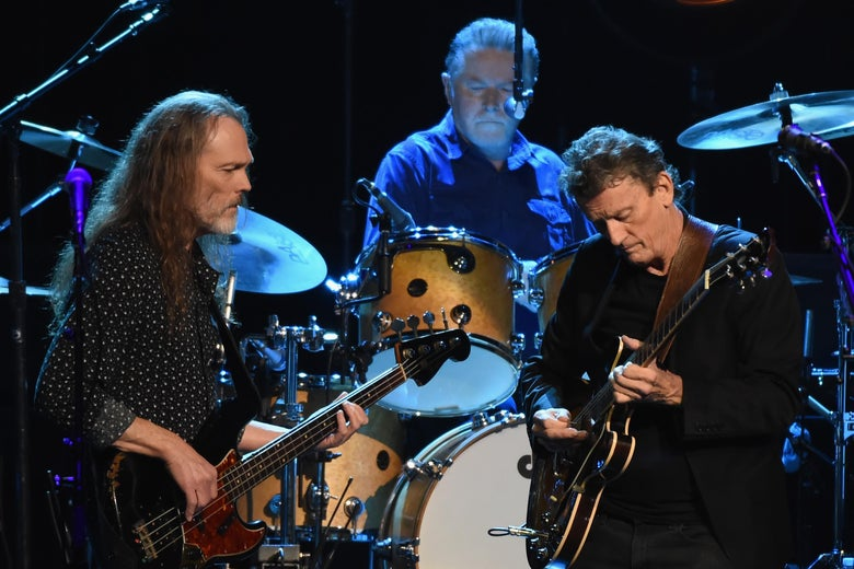 The Eagles perform on a stage bathed in blue light.