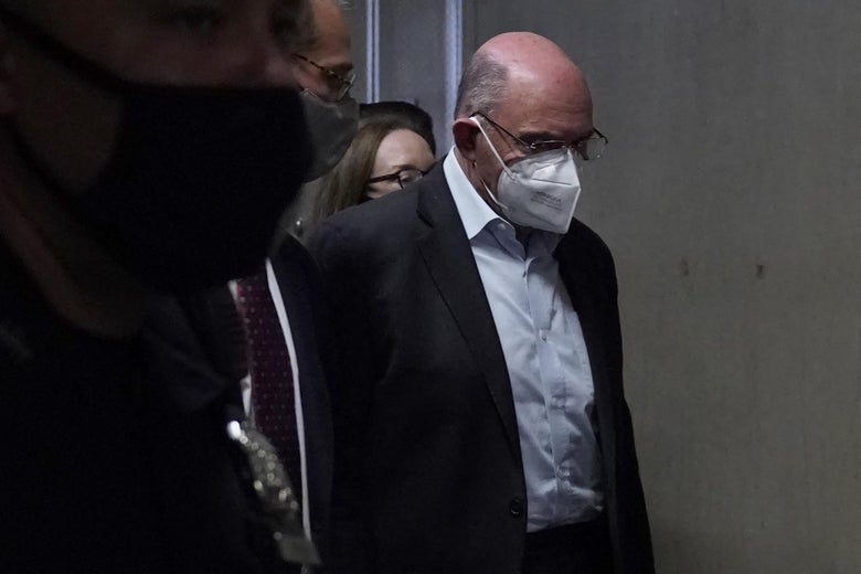 Allen Weisselberg walking in a dim hallway with his head down in a mask.