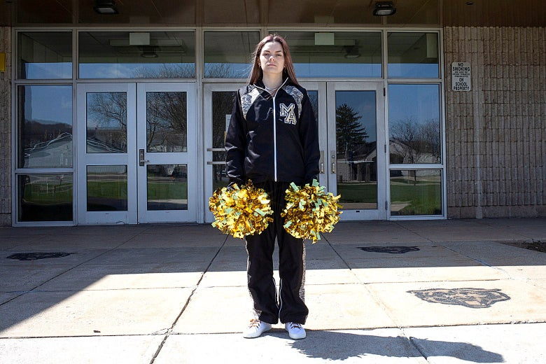A woman in a track suit holds pompoms in front of a school.