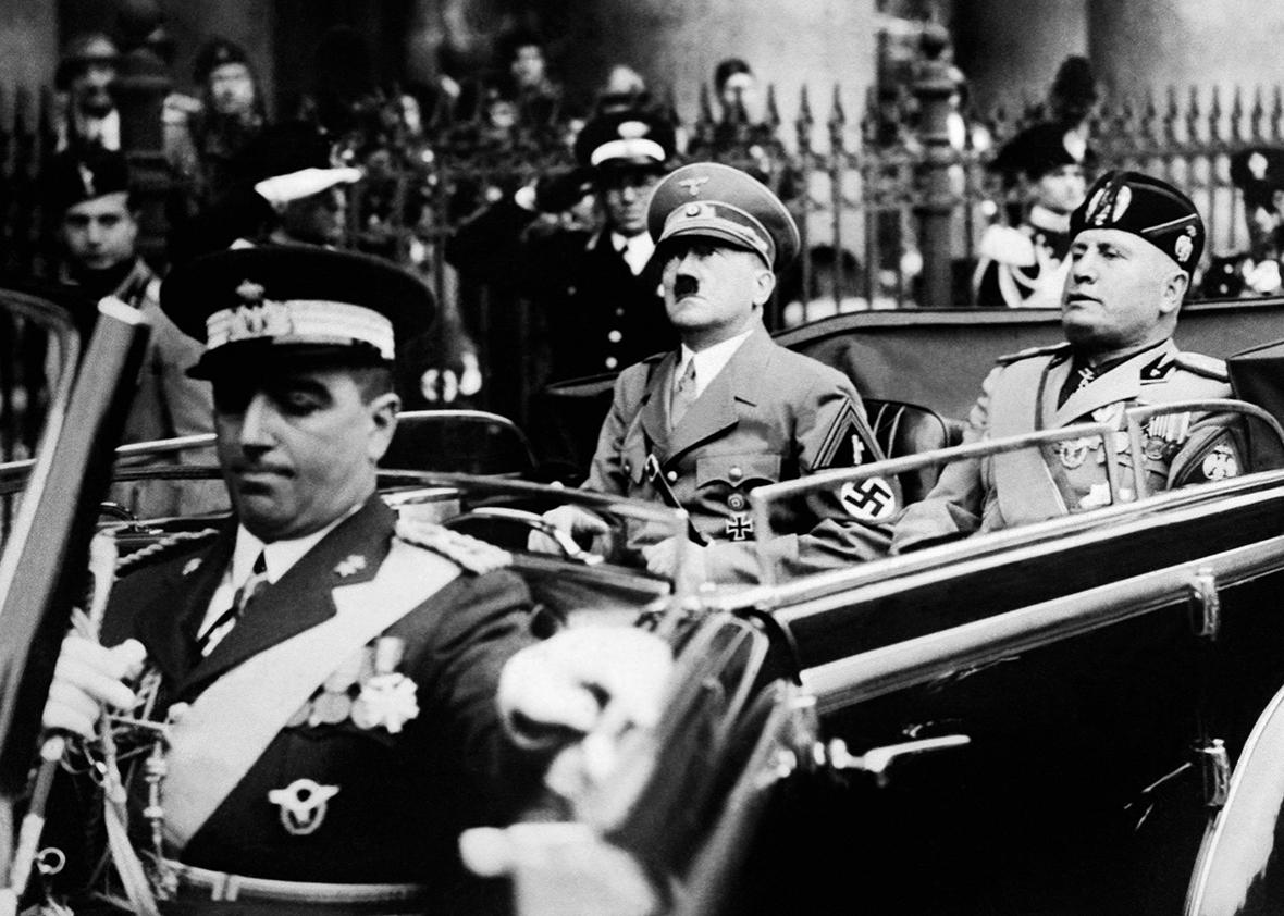 A picture taken in September 1937, in Munich, shows German Chancellor Adolf Hitler riding in a car with Italian dictator Benito Mussolini while the crowd gives the fascist salute.
