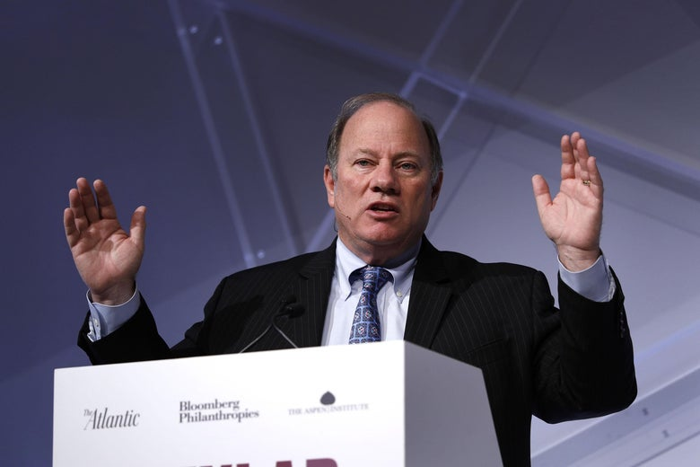 Duggan raises both arms while speaking at a podium