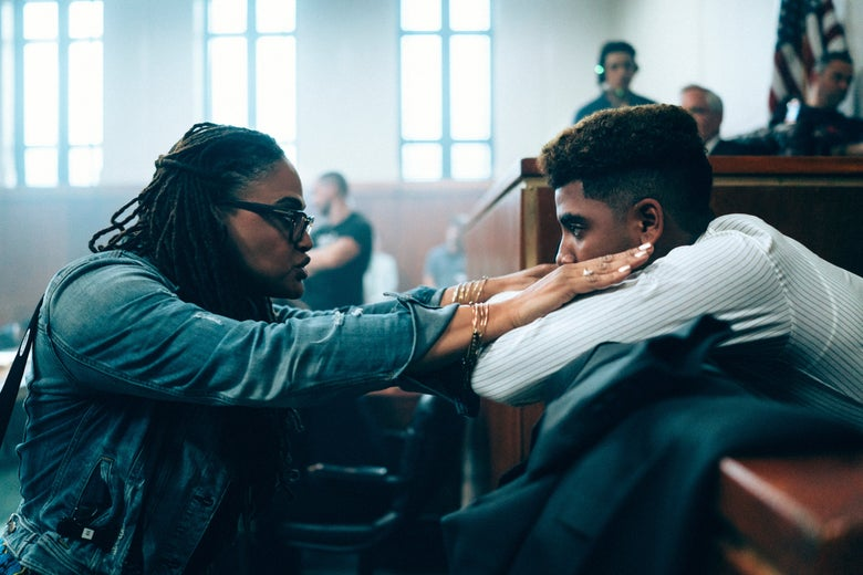 Ava DuVernay and Jharrel Jerome on the set of a courtroom.