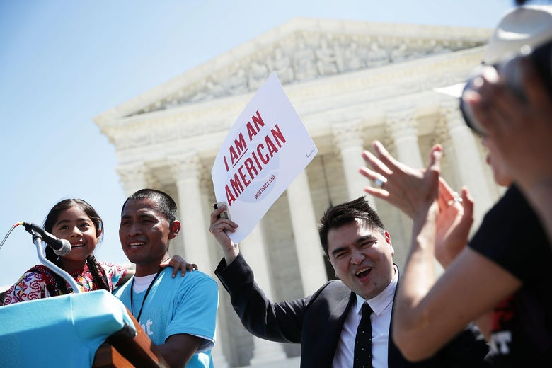 "In front of the U.S. Supreme Court, Sophie Cruz and her father stand behind a podium. Jose Antonio Vargas holds a sign that says, ""I am an American."""