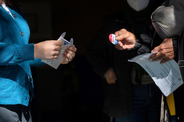 "A voter gets an ""I Voted"" sticker after casting a ballot"