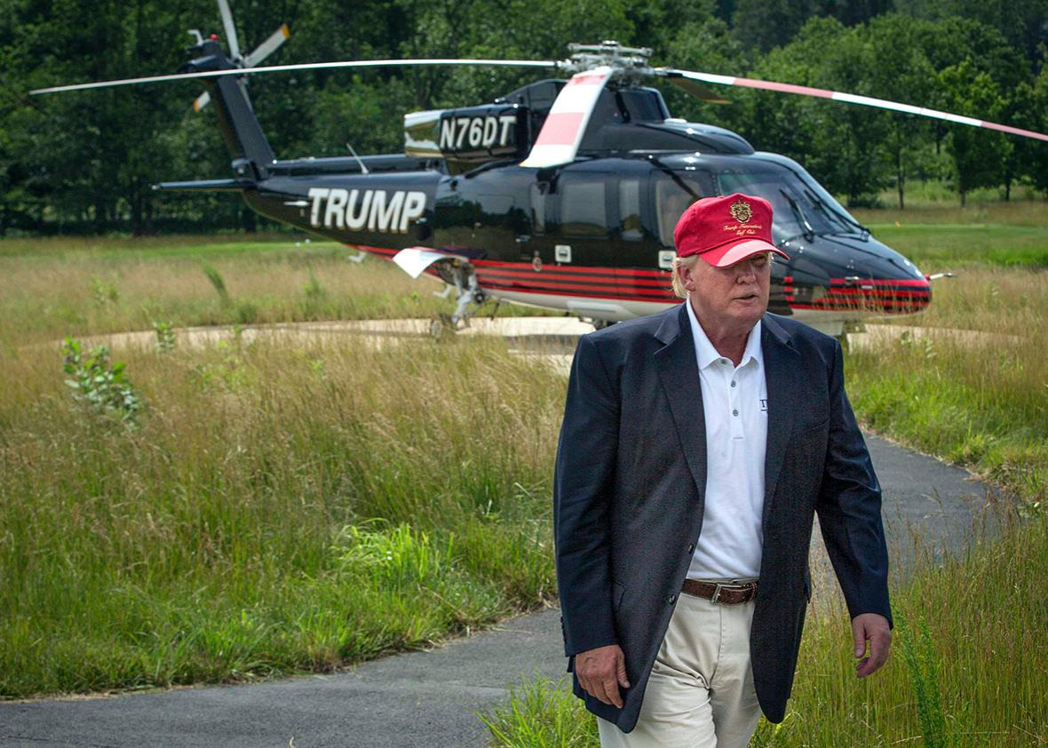 Donald Trump walks past his helicopter.