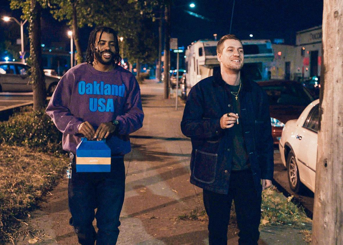 In a scene from Blindspotting, two friends (Daveed Diggs and Rafael Casal) walk down a street in Oakland, California, at night.