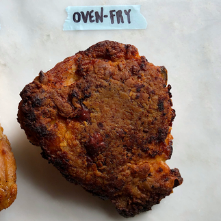 A thickly battered, dark brown chicken thigh labeled Oven + Fry.