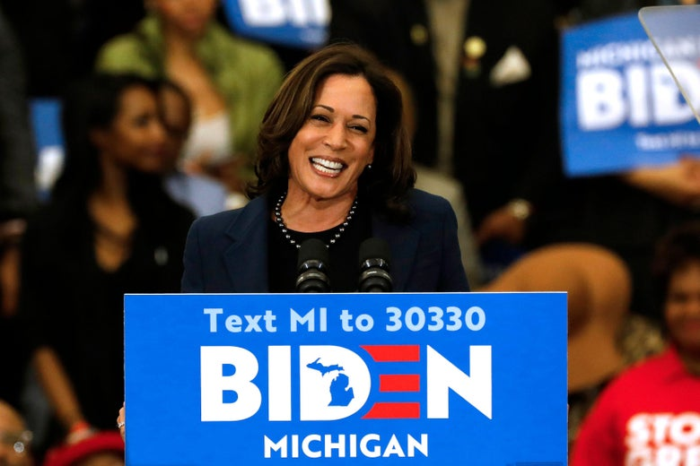 California Sen. Kamala Harris smiles and speaks to supporters at a podium during a Biden campaign rally.
