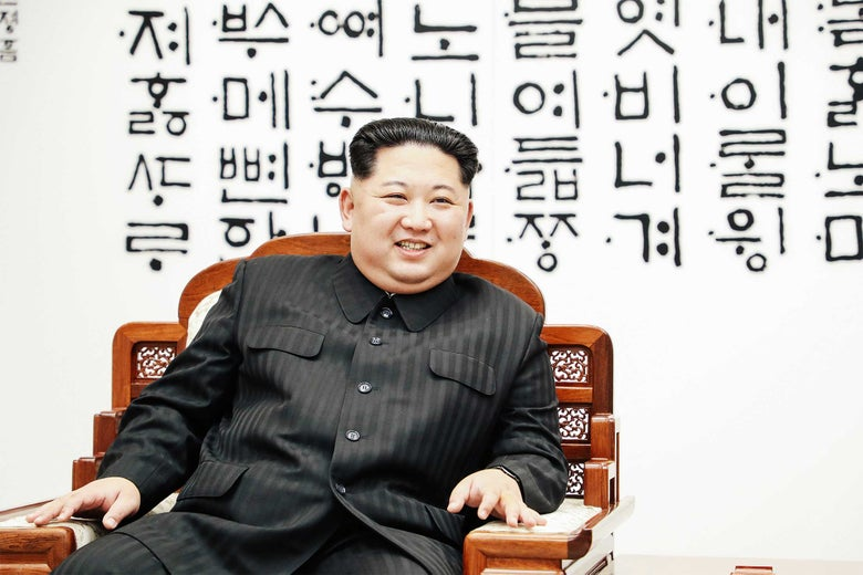 Kim Jong-un sitting in a chair and smiling.