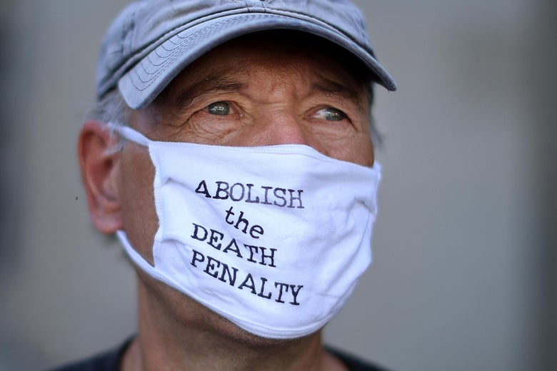 """Laffin stares deeply wearing a mask that says """"Abolish the Death Penalty."""""""