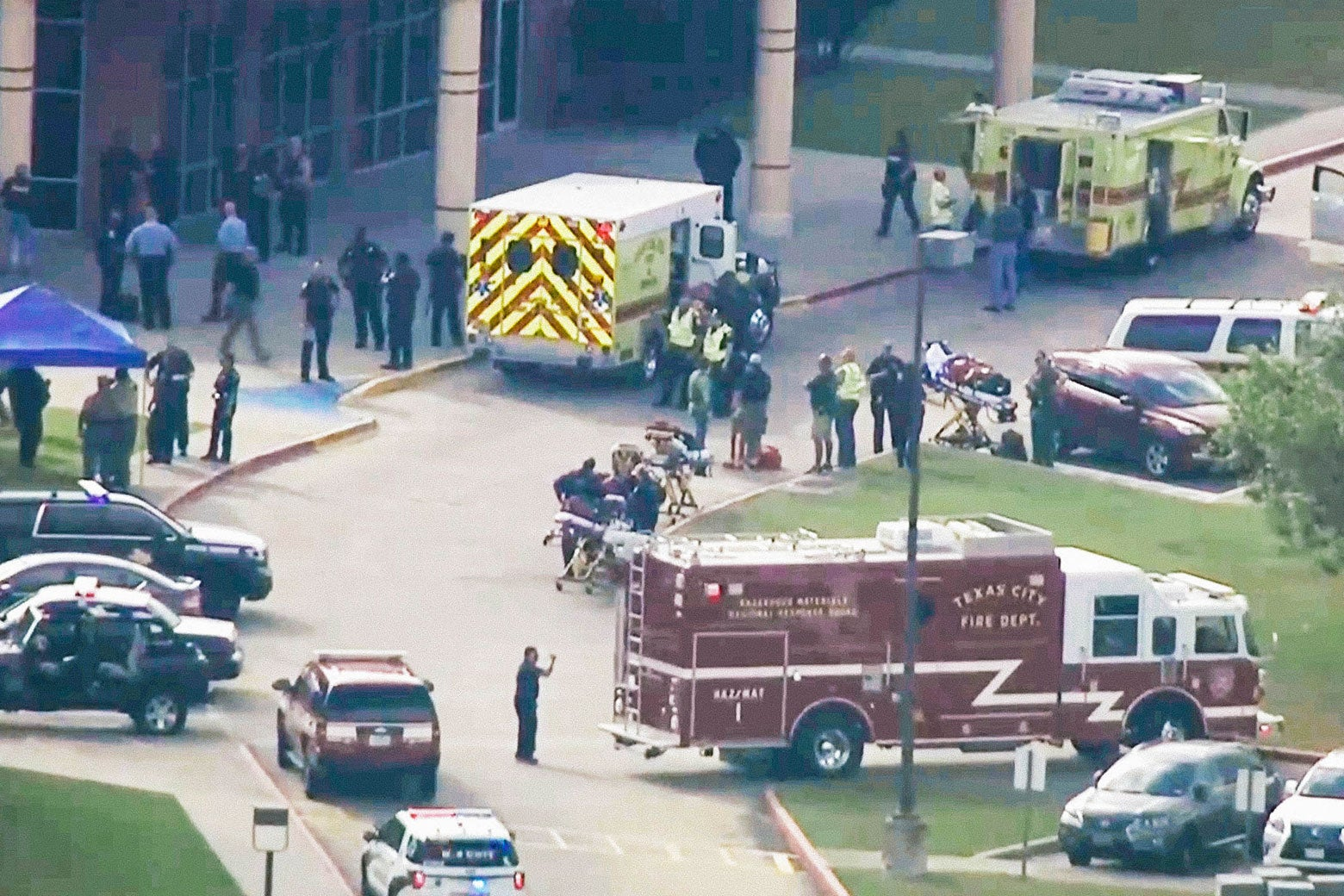 A fire truck, ambulances, and police cars outside a high school as seen from a helicopter.