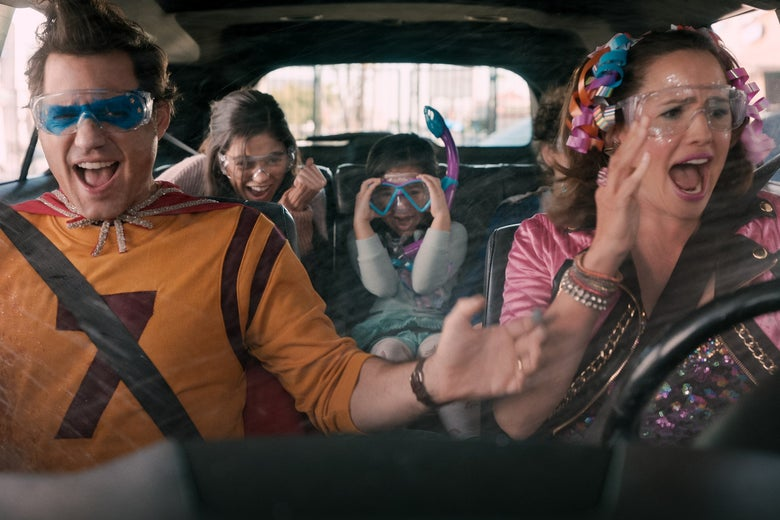 A mom and dad in silly outfits behind the wheel of a minivan getting sprayed while their kids scream gleefully in the back seat