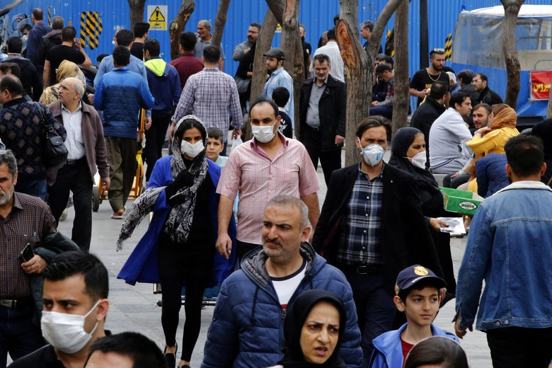 Iranians, some wearing protective masks, walk down the street in Tehran.