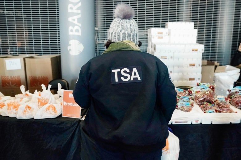 The back of a person in a TSA jacket as they look at packaged food on a table.