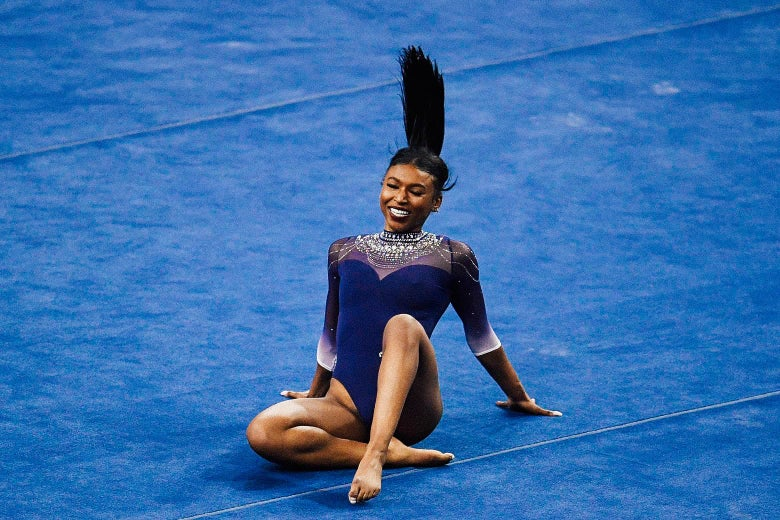 Nia Dennis beaming during her floor exercise, seated cross legged with her hands behind her and her ponytail in the air.