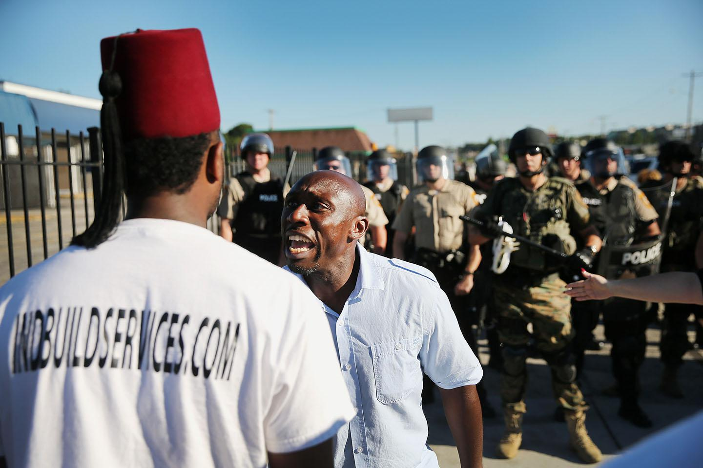 A demonstrator, protesting the shooting death of teenager Michael Brown, pleads with another to walk away after being ordered off the street by police on August 13, 2014 in Ferguson, Missouri.
