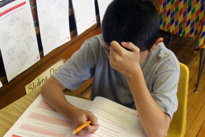 A middle school student holding a pencil works to solve a problem at a desk.