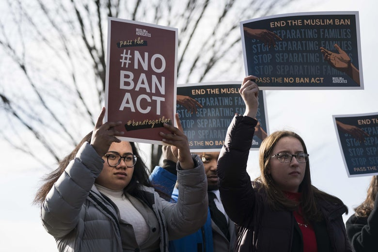 """People hold signs reading """"#NoBanAct"""" and """"End the Muslim Ban."""""""