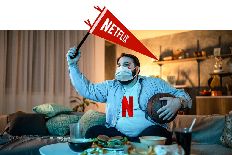 A fan of Netflix sits on his couch, wearing his Netflix jersey, waving his Netflix pennant, wearing a surgical mask