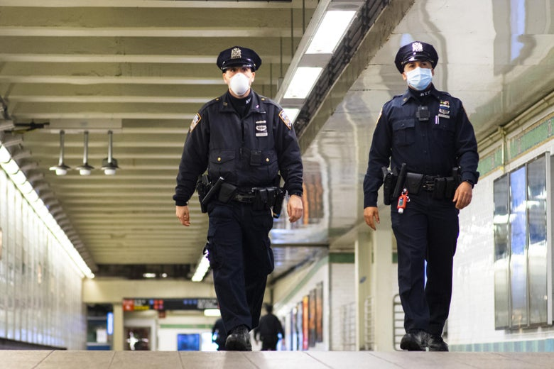 NYPD officers wearing face masks patrol inside a subway station.
