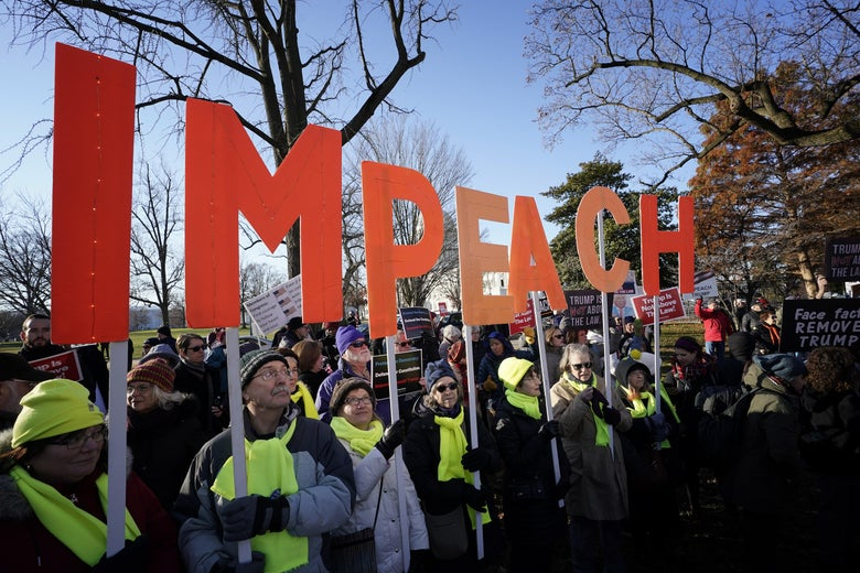 "Protesters outside the capitol hold signs that read ""IMPEACH."""