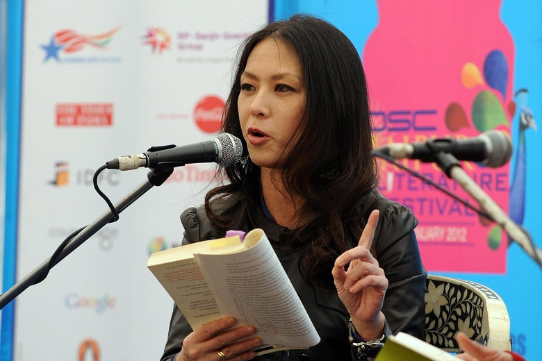 Amy Chua gestures with one hand as she reads from her book at a mic.