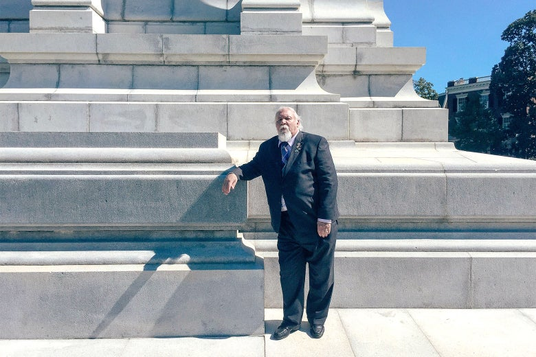 Frank Earnest of the Virginia Division of the Sons of Confederate Veterans stands at the base of the Robert E. Lee memorial on Monument Avenue in Richmond, Virginia.